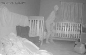 The camera captured a ghostly horned figure near the bed with a child